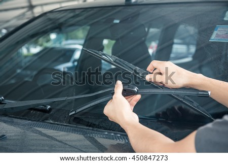 Man is changing windscreen wipers on a car Royalty-Free Stock Photo #450847273