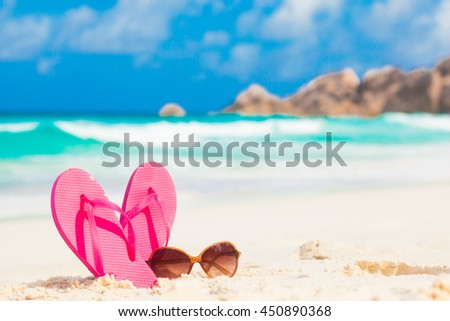 Pink flip flops and sunglasses on a tropical sea resort background #450890368