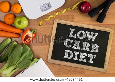 LOW CARB DIET Fitness and weight loss concept, dumbbells, white scale, fruit and tape measure on a wooden table, top view, free copy space Royalty-Free Stock Photo #450944614