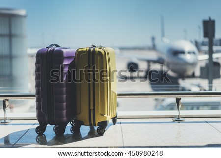 Suitcases in airport departure lounge, airplane in background, summer vacation concept, traveler suitcases in airport terminal waiting area, empty hall interior with large windows, focus on suitcases Royalty-Free Stock Photo #450980248