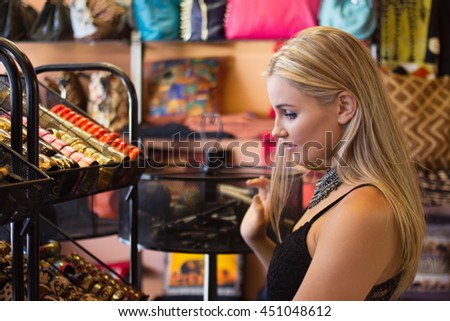 Pretty Blonde female looking at merchandise in a shopping mall #451048612