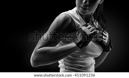 Black and white close up portrait of fitness athletic young woman in sports clothing showing her well trained body, six pack, perfect abs, shoulders, biceps, triceps and chest, deltoid muscle. #451091236
