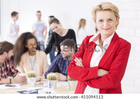 Middle aged professional elegant boss of a successful company. Behind her corporation's management during a meeting Royalty-Free Stock Photo #451094113