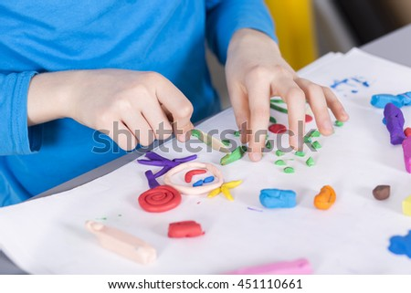 Close-up of little creative boy doing a picture on a paper with a colorful plasticine #451110661