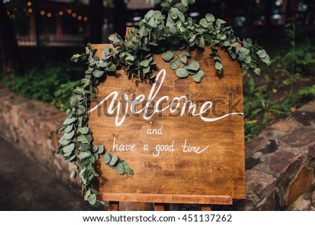 Handmade wooden board with welcome sign on it decorated with eucalyptus. Wedding. Reception.