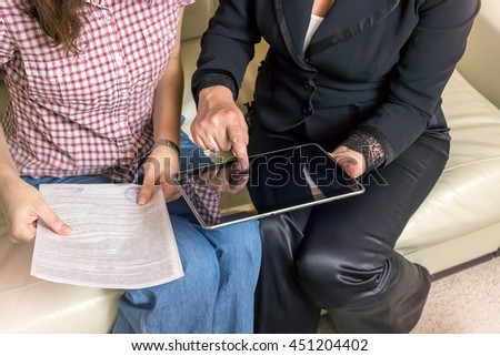 The insurance agent makes a deal, sign documents. The tablet in female hands. A woman touching the screen with her finger. #451204402