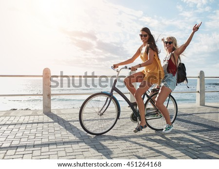 Joyful young women riding a bicycle together. Best friends having fun on a bike at the seaside promenade. #451264168