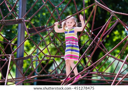 Active little child playing on climbing net and jumping on trampoline at school yard playground. Kids play and climb outdoors on sunny summer day. Cute girl on nest swing at preschool sport center. #451278475