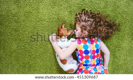 Little girl embracing puppy jack russell. High top view. #451309687