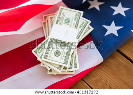 budget, finance and nationalism concept - close up of american flag and dollar cash money packets #451317292