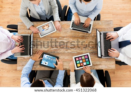 business, people, media and technology concept - close up of creative team with laptop and tablet pc computers sitting at table in office