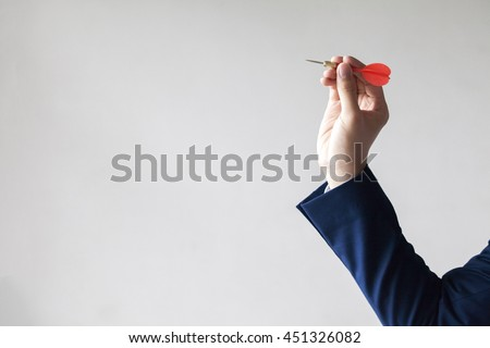 Businessman holding a dart aiming at the target - business targeting, aiming, focus concept. #451326082