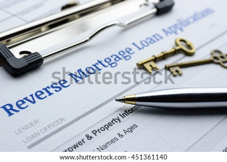 Blue ballpoint pen, two vintage brass keys and a reverse mortgage loan application on a clipboard. A blank document is waiting to be completed by a homeowner who want to turn their asset into cash. #451361140