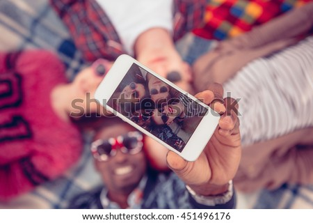 Toned. Picture of best friends making selfie on mobile or smart phone while spending free time on picnic in parkland.