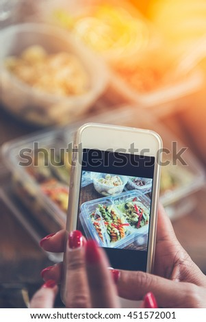 Close up of woman hands clicking picture of food. Woman using smartphone for food photography.female hands taking photo of pasta curry lunch box and chiken with smart phone.