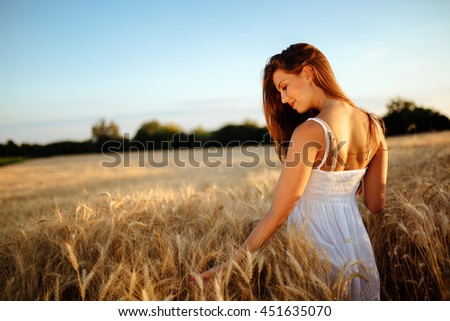 Romantic woman walking in golden fields of barley #451635070