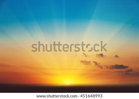 Beautiful blazing sunset landscape at over the meadow and orange sky above it. Amazing summer sunrise as a background.  Royalty-Free Stock Photo #451648993
