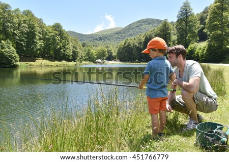 Father and son fishing together by mountain lake #451766779