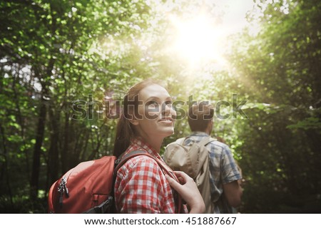 adventure, travel, tourism, hike and people concept - group of smiling friends walking with backpacks in woods #451887667