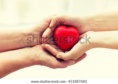 people, age, family, love and health care concept - close up of senior woman and young woman hands holding red heart #451887682