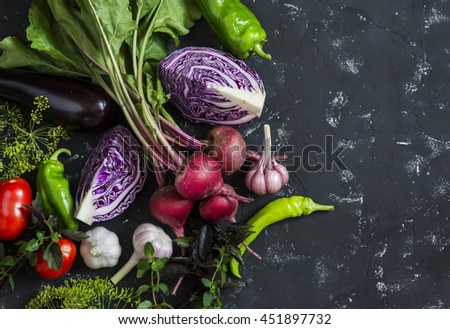 Fresh vegetables - red cabbage, beets, eggplant, peppers, garlic, tomatoes, herbs on a dark background. Raw ingredients. Food background #451897732