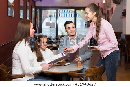 Smiling friendly young waitress serving family of three at cafe table. Selective focus on guy #451940629