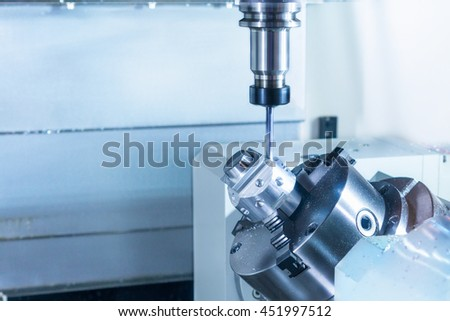 CNC milling machine during operation. Produce drill holes in the metal part. #451997512