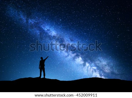 Milky Way. Silhouette of a standing man pointing finger in night starry sky on the mountain. Colorful night landscape with beautiful universe. Travel background with blue sky and amazing Milky Way