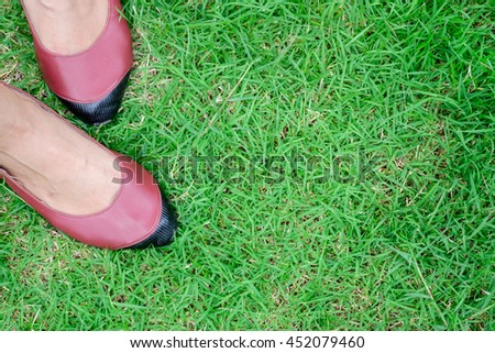 close up on fashion handmade red and black leather shoes for small feet woman on green grass background #452079460