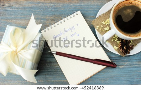 Good morning message theme:surprise for love person with cup of fresh tasty coffee decorated with natural piny cone and dry petals of hydrangea, small gift box and notebook with inscription