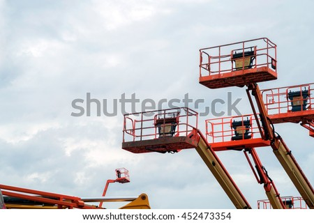 The Used Red Boom Lifts with the blue sky background in the warehouse for sale #452473354