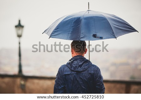 Rainy day. Young man is holding blue umbrella and walking in rain. Street of Prague, Czech Republic. - selective focus on person #452725810