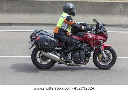 FRANKFURT, GERMANY - JULY 12, 2016: Motorcyclist on a Honda motorcycle driving on the highway in Germany #452732524