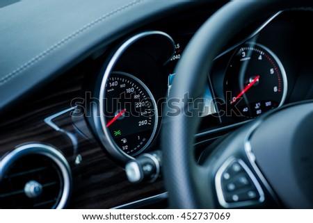 Luxury car interior details. Speedometer and steering wheel Royalty-Free Stock Photo #452737069