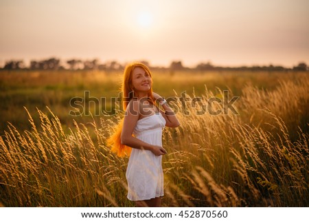 Young beautiful red-haired girl in a field at sunset, looking into the camera #452870560