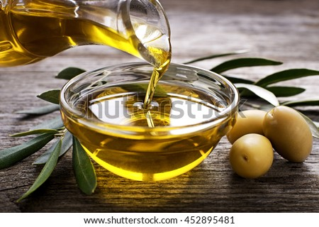 Bottle pouring virgin olive oil in a bowl close up Royalty-Free Stock Photo #452895481