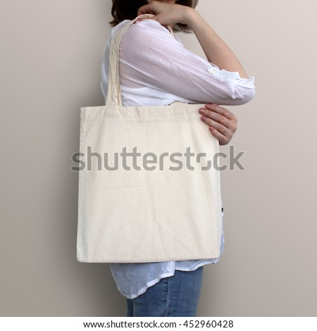 Mock-up. Girl is holding blank cotton tote bag. #452960428