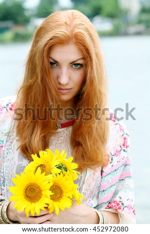 Closeup portrait of beautiful young fashion model with long red haired wavy hair posing wearing bohemian kimono, beige lace shirt, necklace and bracelet standing at the beach on sunny summer day.