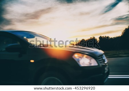 car moving rapidly on the road. car driving on the road in the rays of the setting sun. side view. blurred background and blurred motion due to the concept #453296920