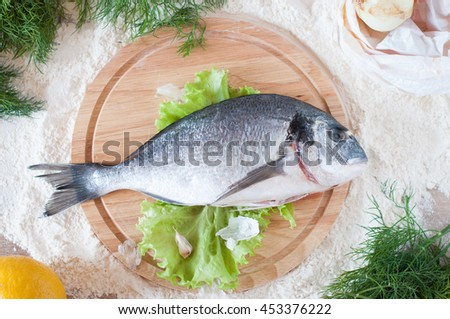 raw fish dorado table flat lay on a round cutting board #453376222