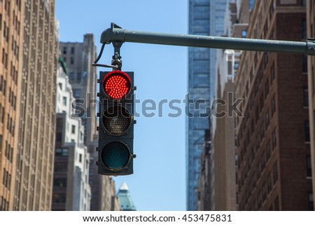 Traffic light on the background of skyscrapers in New York. Glowing red light. Traffic lights showing red color. #453475831