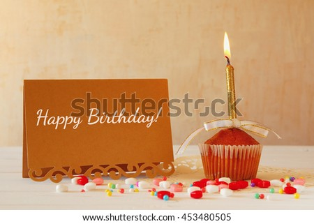 Birthday concept with cupcake and candle next to greeting card on wooden table