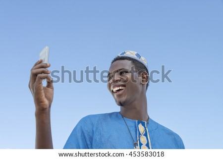Young man making a self-portrait with his mobile phone under a blue sky    #453583018