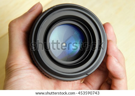 Hand hold camera dslr lens with nice lighting shining on the lens #453590743
