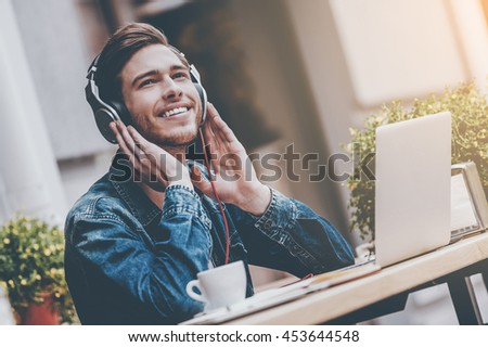 What a great day! Cheerful young man holding hands on headphones while sitting at sidewalk cafe #453644548