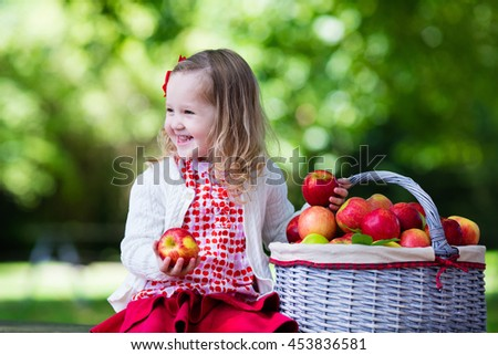 Little girl playing in apple tree orchard.  #453836581