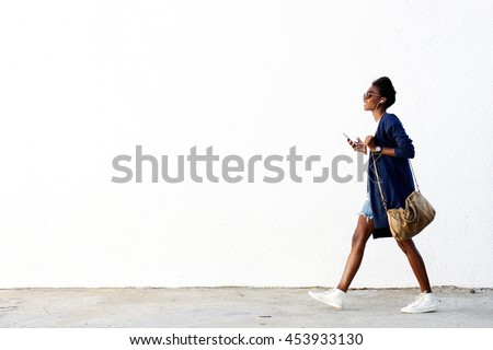 Full length side view portrait of trendy young black woman walking outdoors and listening to music on her mobile phone #453933130