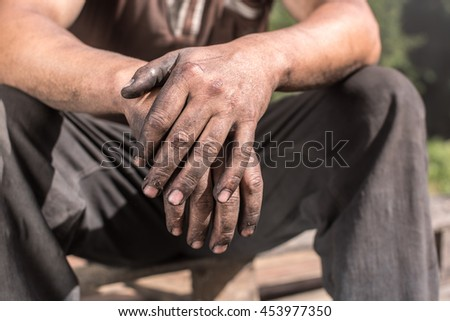 Charcoal-burners worker man with dirty hands. Worker Hands. #453977350