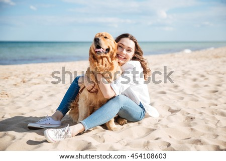 Happy charming young woman sitting and hugging her dog on the beach