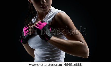 Close up portrait of female bodybuilder wearing gloves ready for gym exercise. Horizontal studio shot with copy space on black background #454516888